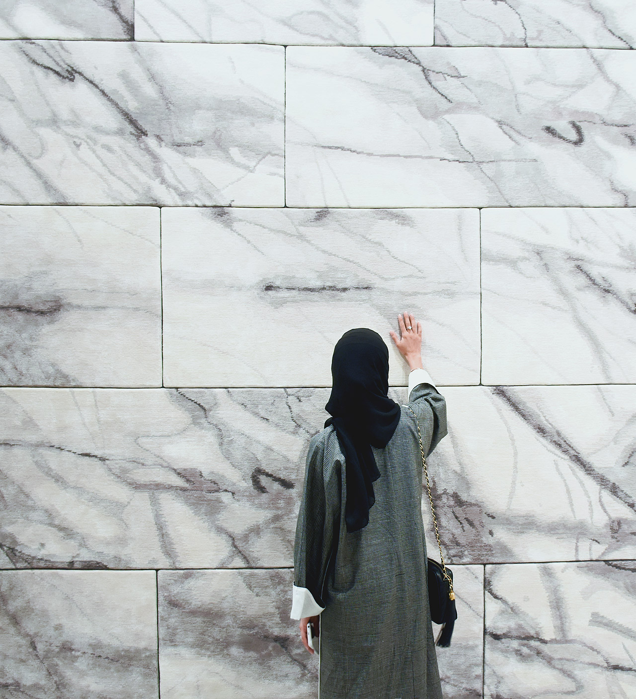Dubai-based designer Aljoud Lootah interacts with the softest marble tiles in the world from the Floor to Heaven series by Michaela Schleypen at Samovar Carpets during Downtown Design Dubai 2016.