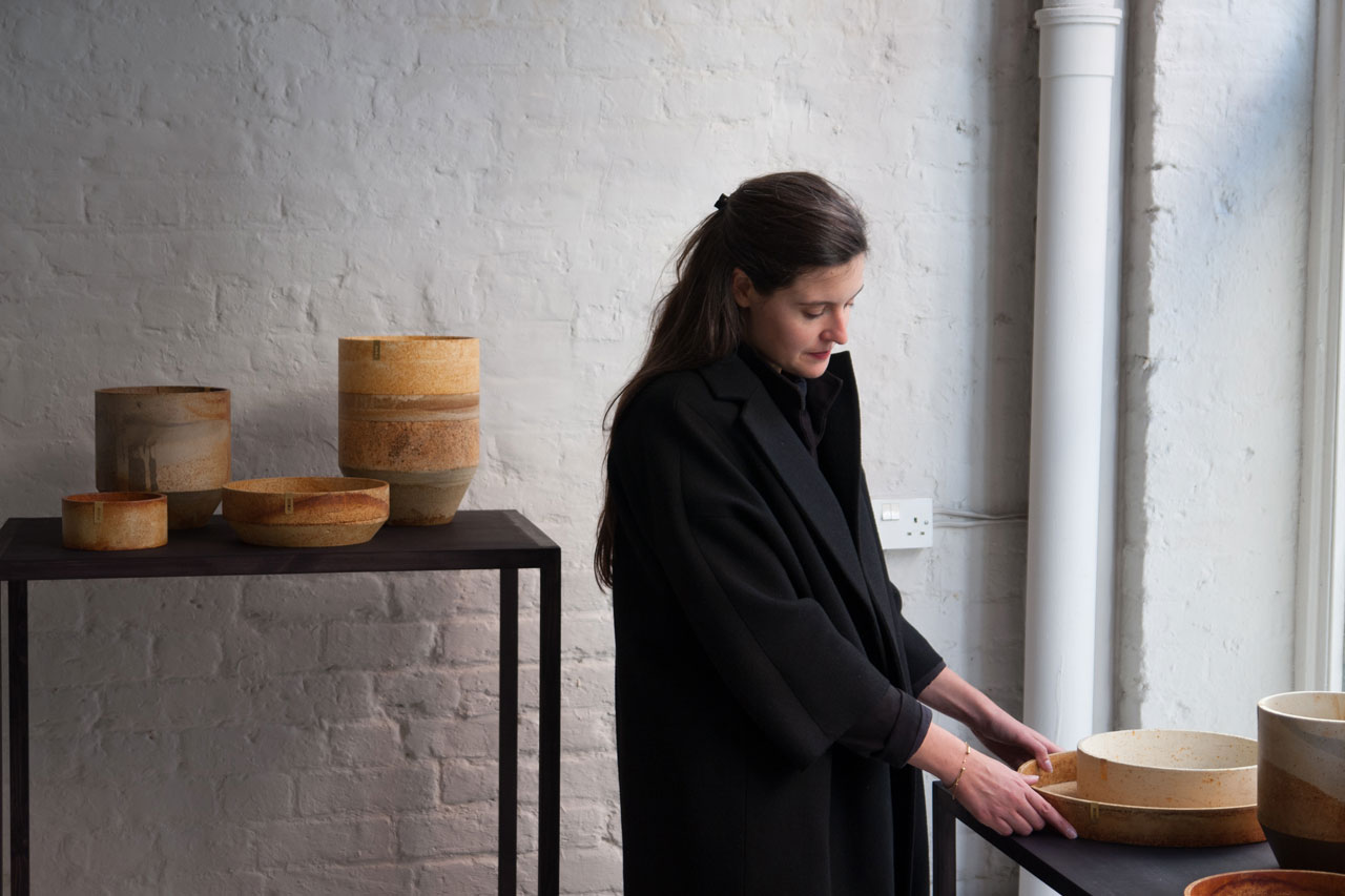A portrait of French designer Ariane Prin in front of herlatest collection in the RUST homeware range byTommaso Lanza.