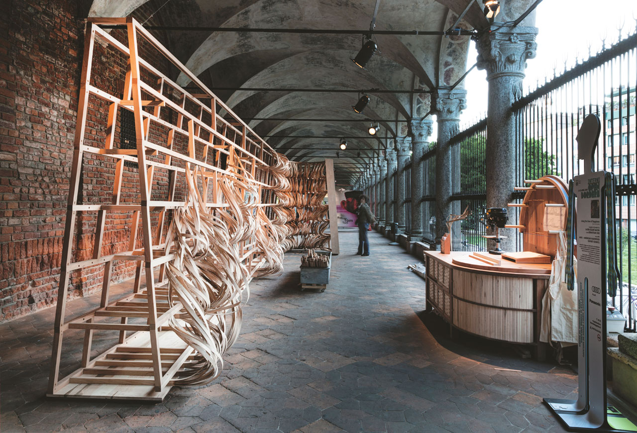 "Designer  Sebastian Cox and sculptor  Laura  Ellen  Bacon bended, folded and intertwined thin  strips  of wood  to  create the ""Along The Lines of Happiness"" at Porticato Largo Richini at University Estatale of Milan / 3 metres high and 9 metres long / American soft maple, American cherry and American red oak.   A project initiated by the American Hardwood Export Council. Photo by Giovanni Nardi."