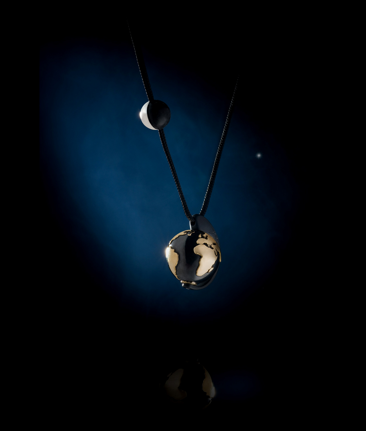 Earth and Moon, 2008, silver & gold, black cord. Photo by Alexandros Botonakis.