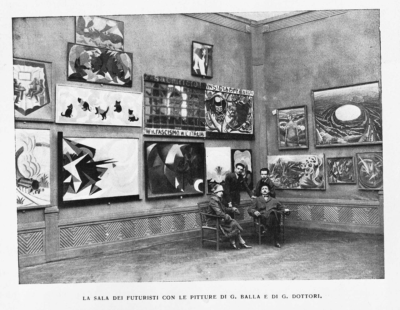 Installation view of III Biennale di Roma 1925 – Futurist group show curated by F. T. Marinetti. Wall A: works by Giacomo Balla, Fortunato Depero and Gerardo Dottori Among the exhibited works, Canaringatti - Gatti futuristi (1923-1924) by Giacomo Balla - For the work © Giacomo Balla by SIAE 2018. Image published in the magazine EMPORIUM. Archive E. Gigli, Roma.