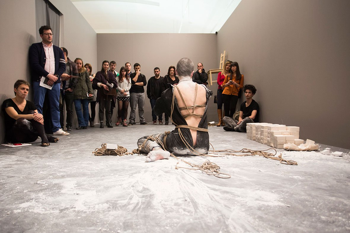 "A group of visitors watch Despina Zacharopoulou perform ""Corner Time"". Photo © Natalia Tsoukalas."