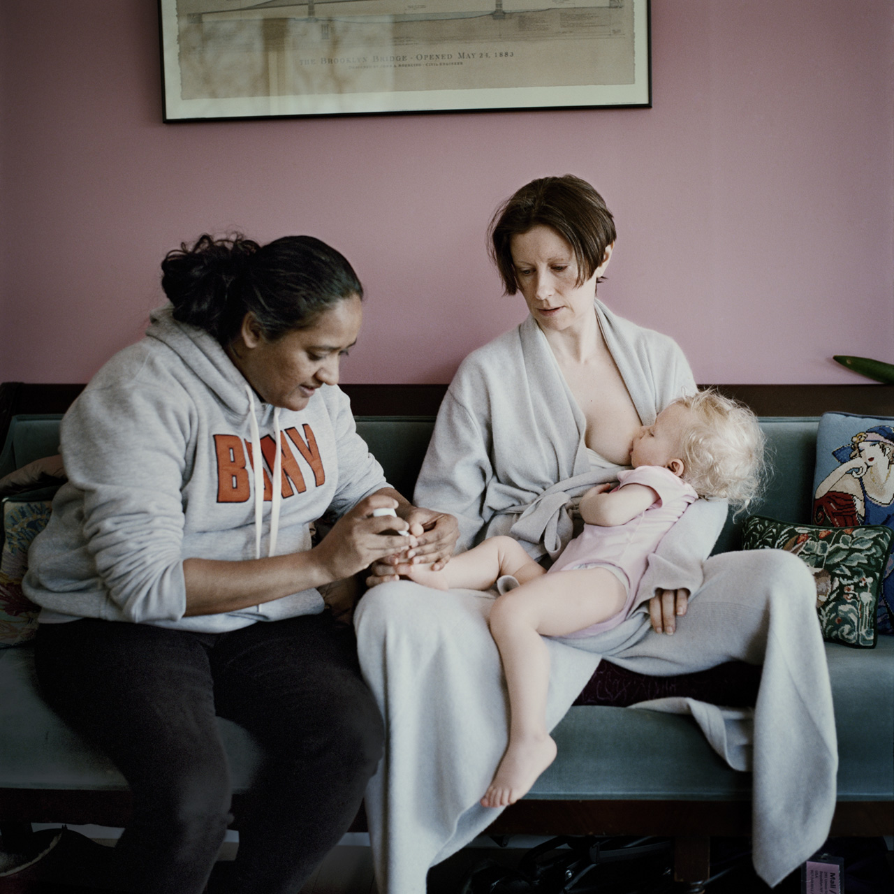 Rachel nurses her 16 month old daughter Michaela while her nanny, Annie, clips the child's toe nails in Brooklyn. Anastasia Taylor-Lind, Not Yet Titled, 2019. © Anastasia Taylor-Lind Fotografiska/TIME.