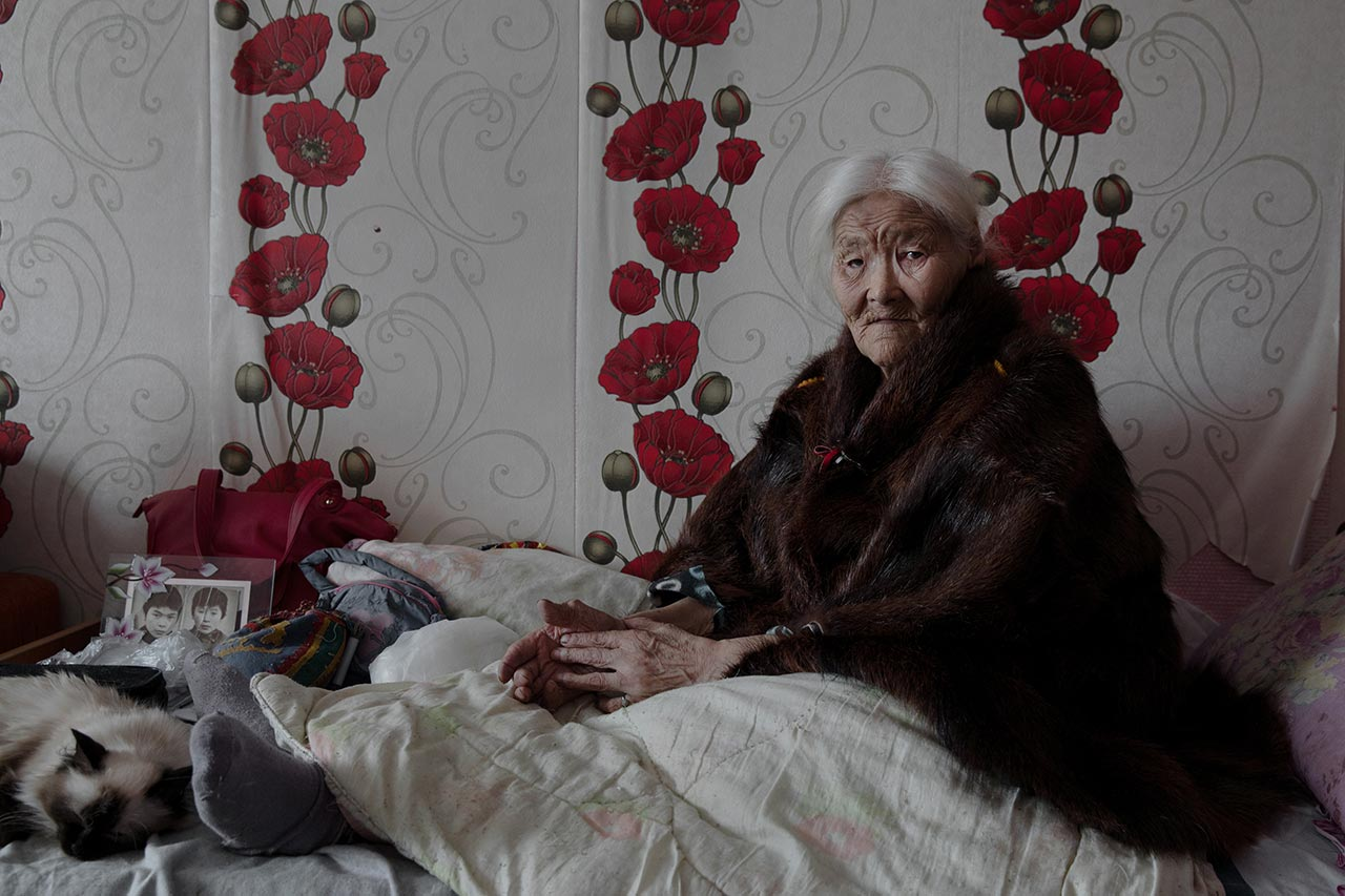 Necla Audi (Born. 1928). Yar-Sale, Yamalo-Nenets Autonomous Okrug, Russia. Although Necla was 89 when this portrait was taken, she declared that she insists on returning to live with the migrating community. At the far left of her bed, a picture of her two sons, taken when they were young. Now, both of them are herders in the tundra. Photo © Oded Wagenstein.