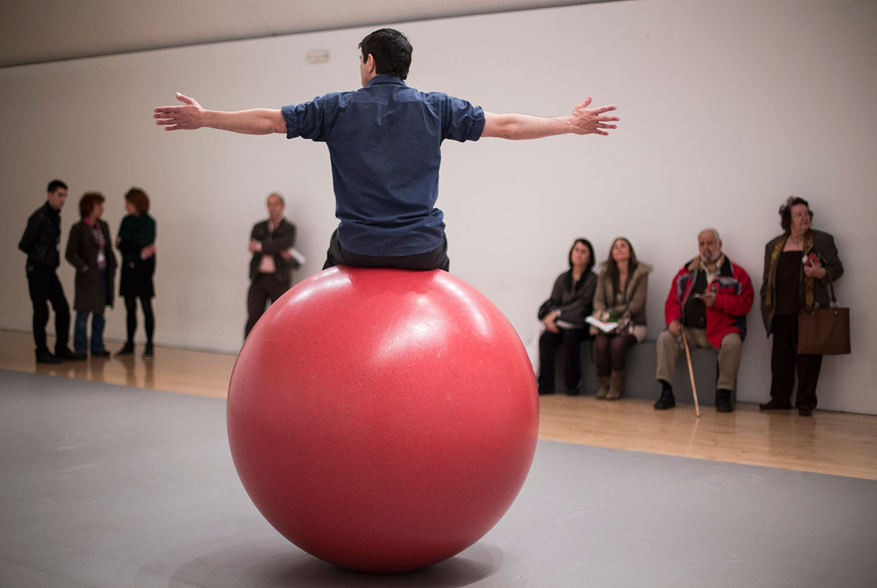 "Dancer Giannis Karounis performs ""Orbital"", where he has to keep his balance on a big red ball for 8 hours. Part of AS ONE at the Benaki Museum, Athens, 2016. Photo © Natalia Tsoukalas."