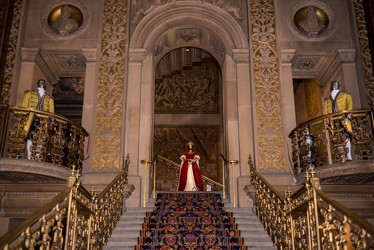 Deborah Devonshire's dress worn for Elizabeth 11 coronation shown at top of stairs in the Painted Hall. Photo courtesy Chatsworth House Trust.