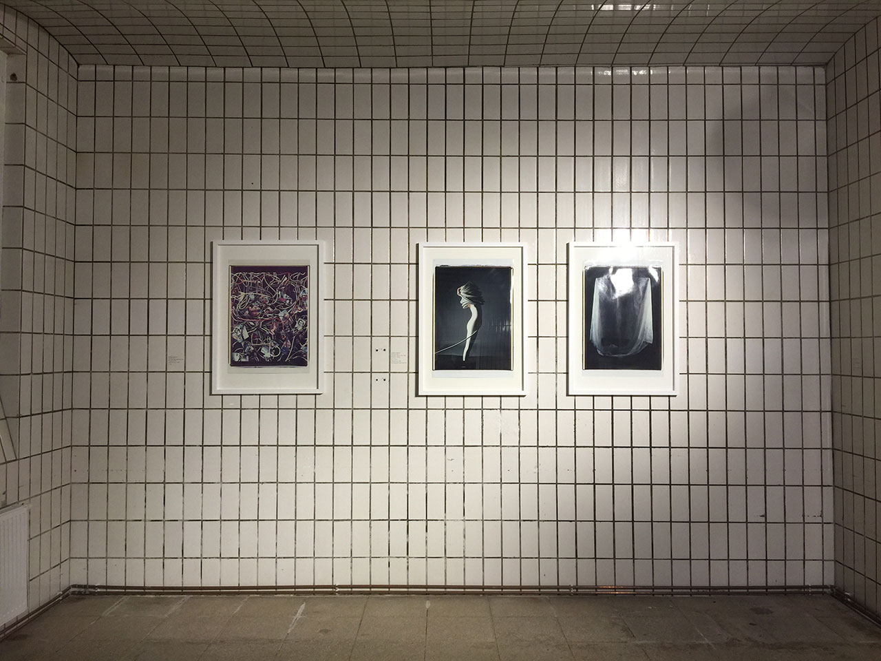 "Installation View from Andrea Jünger Gallery during Open Gallery Night, Vienna Art Week 2016. The basement of Galerie Jünger is a former bakery, completely covered with white tiles. On the wall: photography by Werner Schnelle, from the series ""Mise en Image"", 1982-1986. Photo by Kiriakos Spirou."