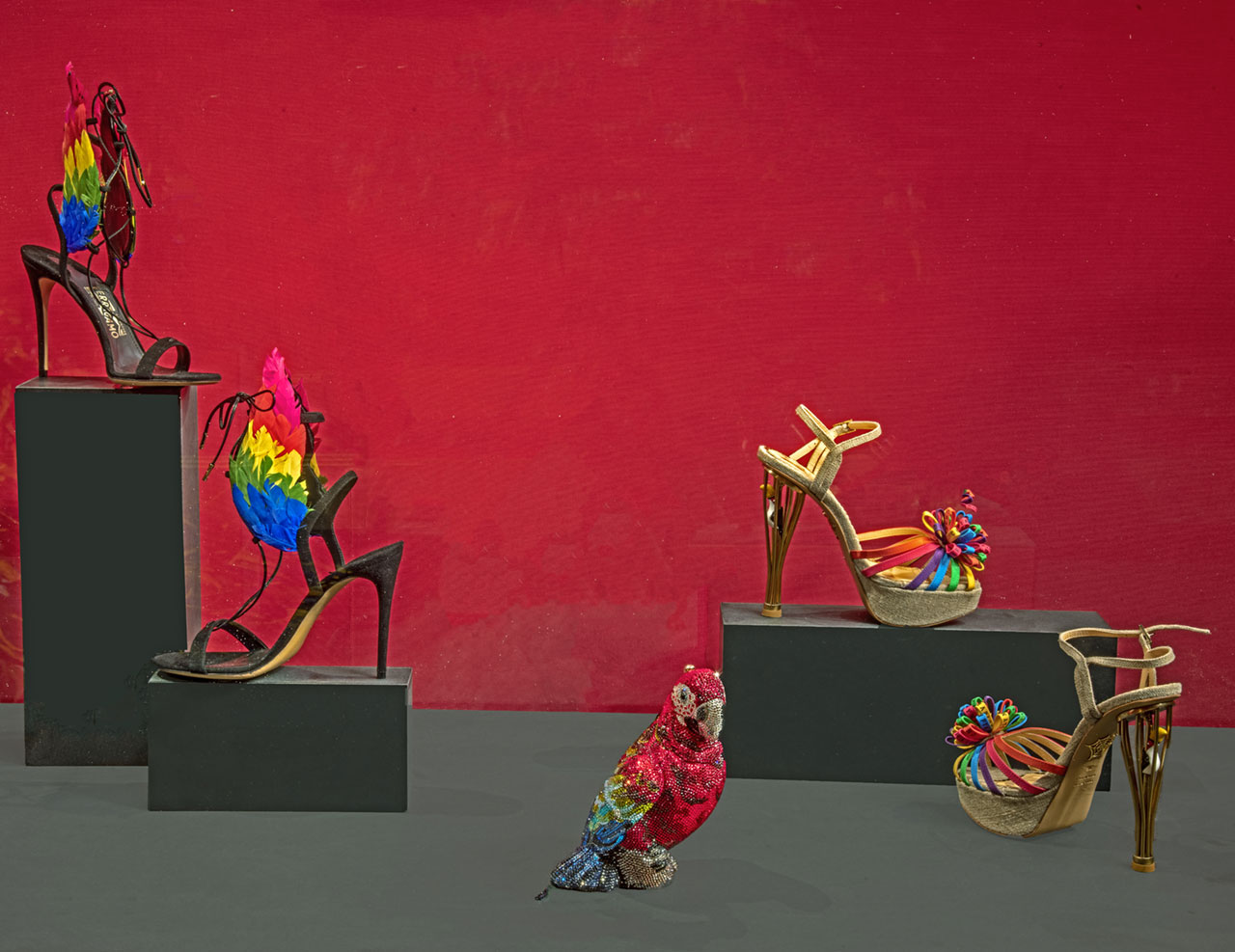 "Exhibition view (from left to right): Salvatore Ferragamo, Sandals. Capsule Collection by Edgardo Osorio, Spring / Summer 2016, Florence, Salvatore Ferragamo Museum. Judith Leiber Couture, ""Scarlet"" parrot clutch, 2018. Charlotte Olympia, ""Birds of Paradise"" sandals, Capsule Collection 2018. Photo © Antonio Quattrone."