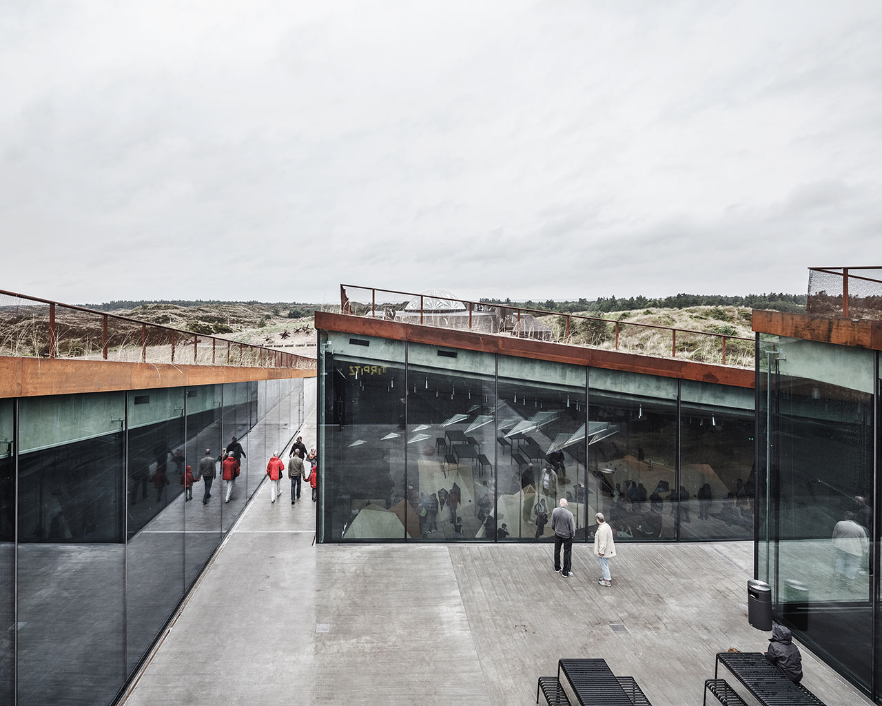 The central courtyard allows access into the four underground gallery spaces that have an abundance of daylight even though they are literally carved into the sand. Photo by Rasmus Hjortshoj.