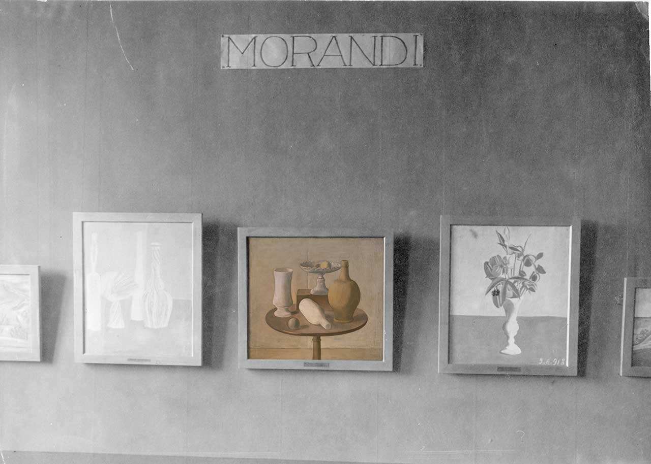 "Rendered photographic image for ""Post Zang Tumb Tuuum"" (Fondazione Prada, Milan, 2018). Installation view of ""Das junge Italien"" at Nationalgalerie Berlin, 1921. Among the exhibited works, Natura Morta (1920) by Giorgio Morandi - For the work © Giorgio Morandi by SIAE 2018."