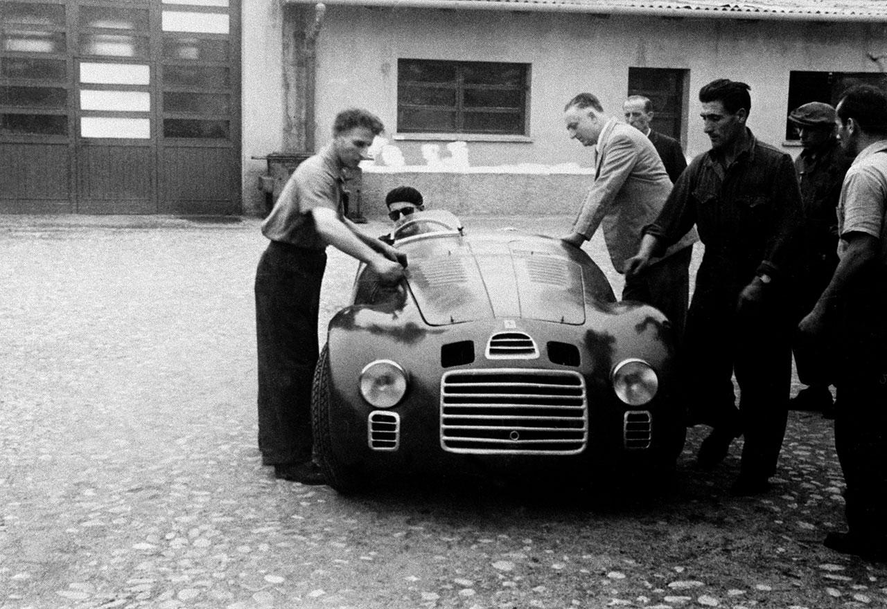 Enzo Ferrari with the 125 S in the courtyard of Fabbrica. At the wheel is Ferdinando Nando Righetti. Photocourtesy of Ferrari.