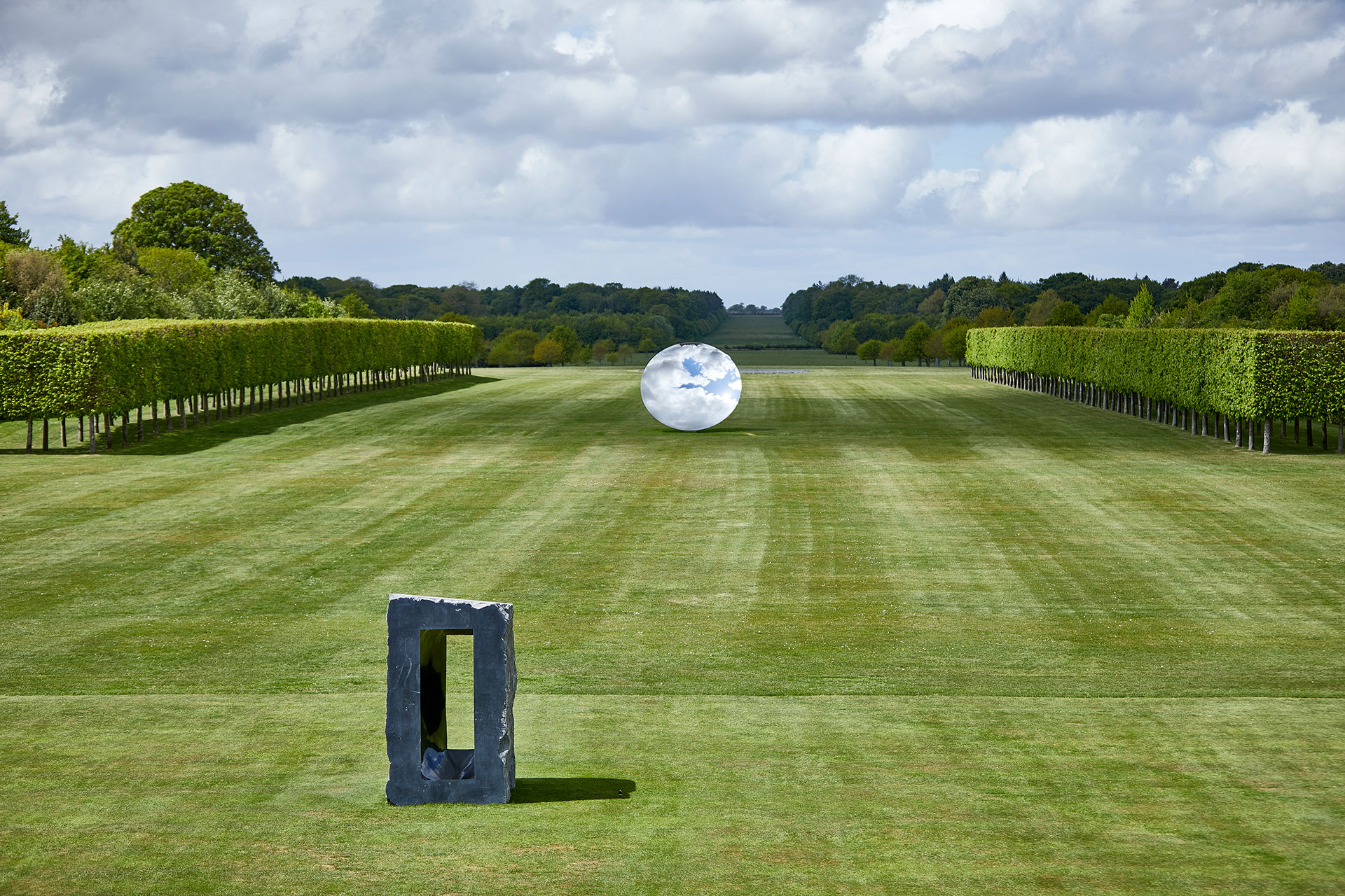 Exhibition view, Anish Kapoor at Houghton Hall. © Anish Kapoor. All rights reserved DACS, 2020. Photo by Pete Huggins. Featured: Sky Mirror, 2018, stainless steel. Courtesy the artist and Lisson Gallery. Untitled, 1997, Kilkenny limestone. Courtesy the artist.