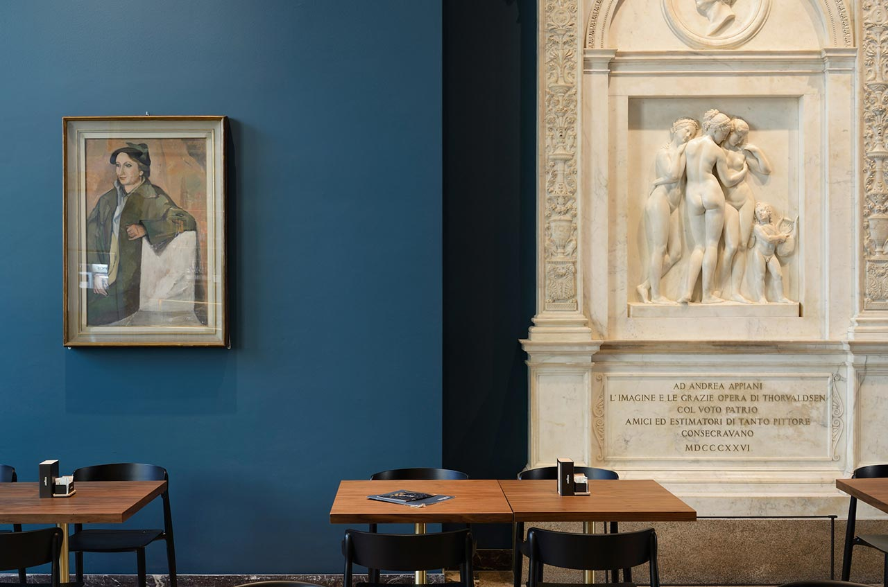 Bertel Thorvaldsen's marble monument to the painter Andrea Appiani depicting Cupid and the Three Graces (right), portrait of Fernanda Wittgens by Attilio Rossi (left). 'Nemea' armchair and 'Inox square' table by Pedrali. Photo by Michele Nastasi.