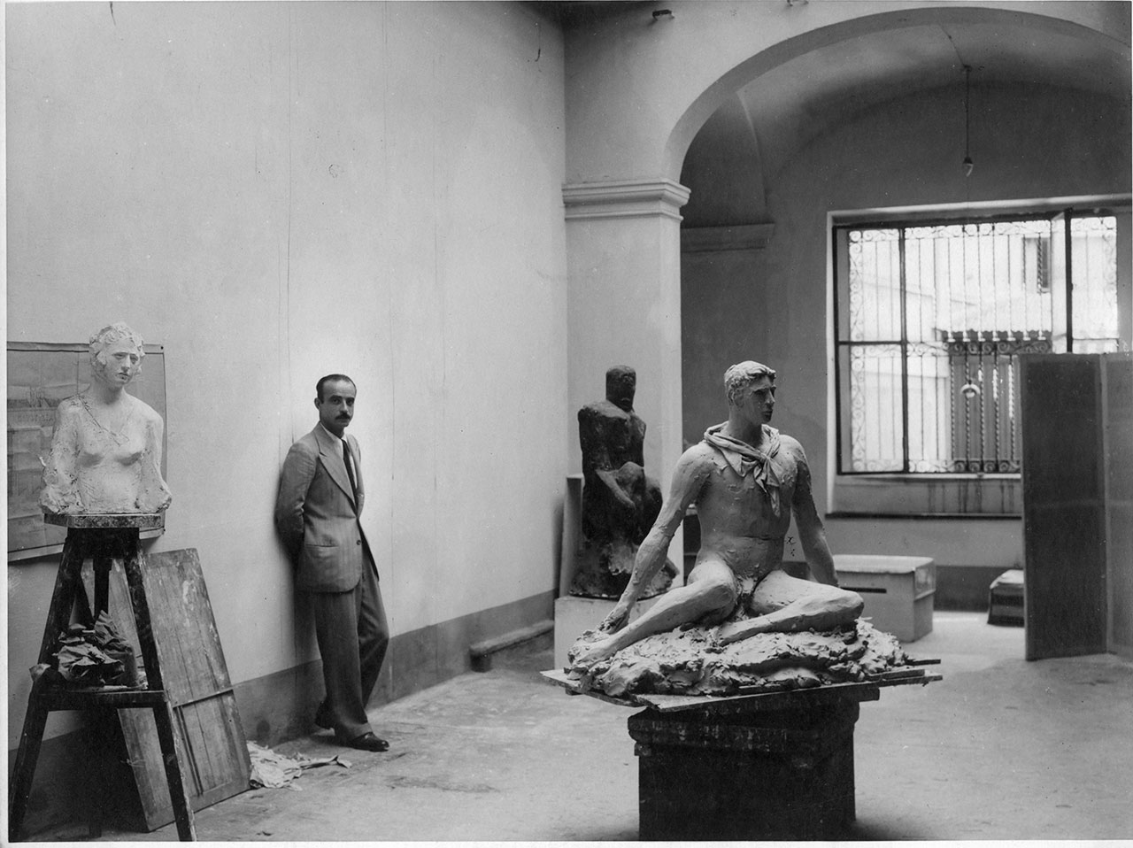 Lucio Fontana in his studio at via De Amicis, Milan 1933. From left to right: Busto di Signorina, Uomo Nero, Uomo seduto (or Atleta in Attesa or Discobolo) for the art works © Fondazione Lucio Fontana © Fondazione Lucio Fontana, Milano by SIAE 2018.