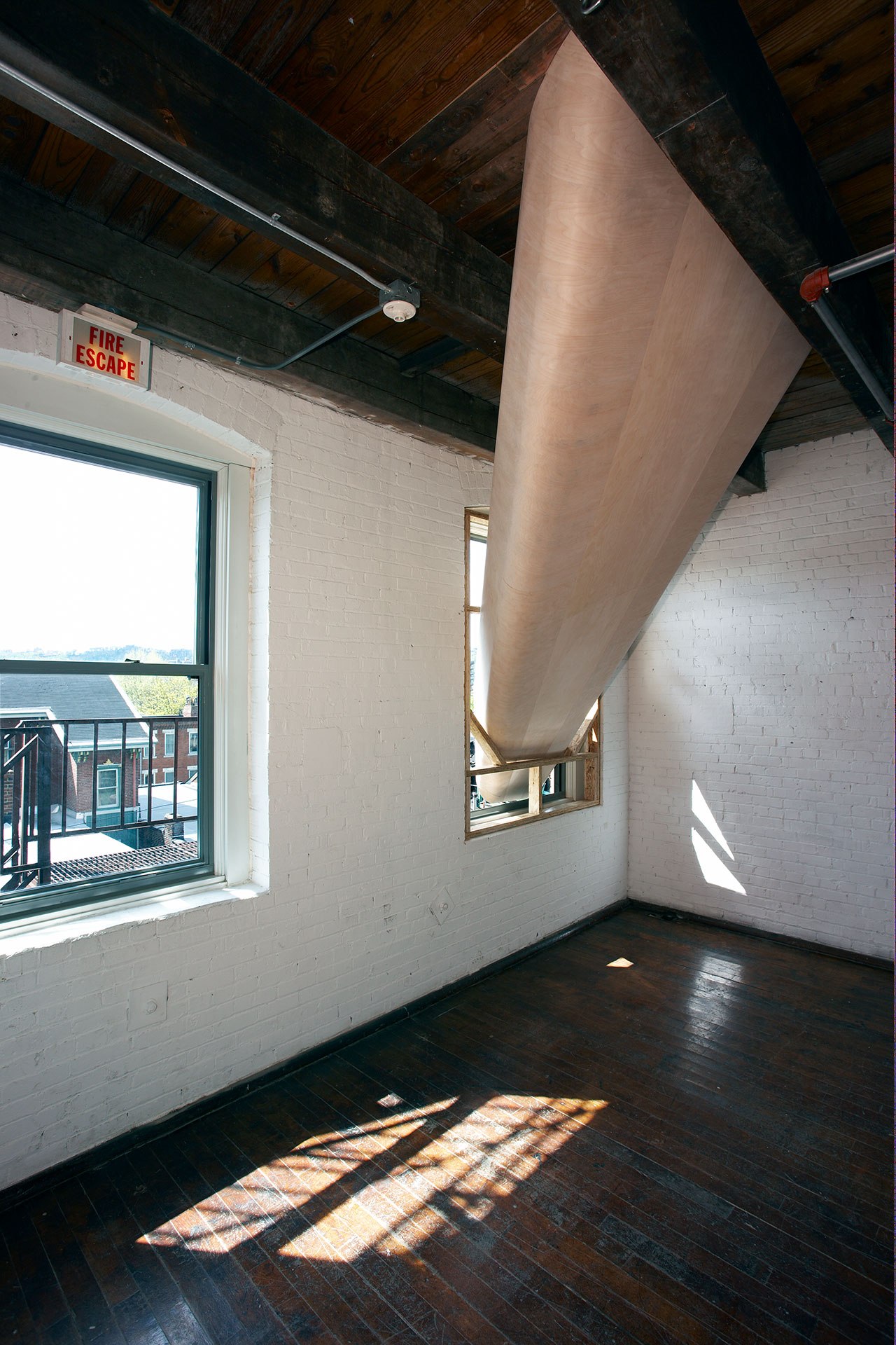 SARAH OPPENHEIMER, 610-3365, 2018.Views from the third and fourth floor.Plywood and existing architecture.Fourth floor opening dimensions: 84″ × 16″.Total dimensions variable.Installation view: Mattress Factory, Pittsburgh, USA, 2008.