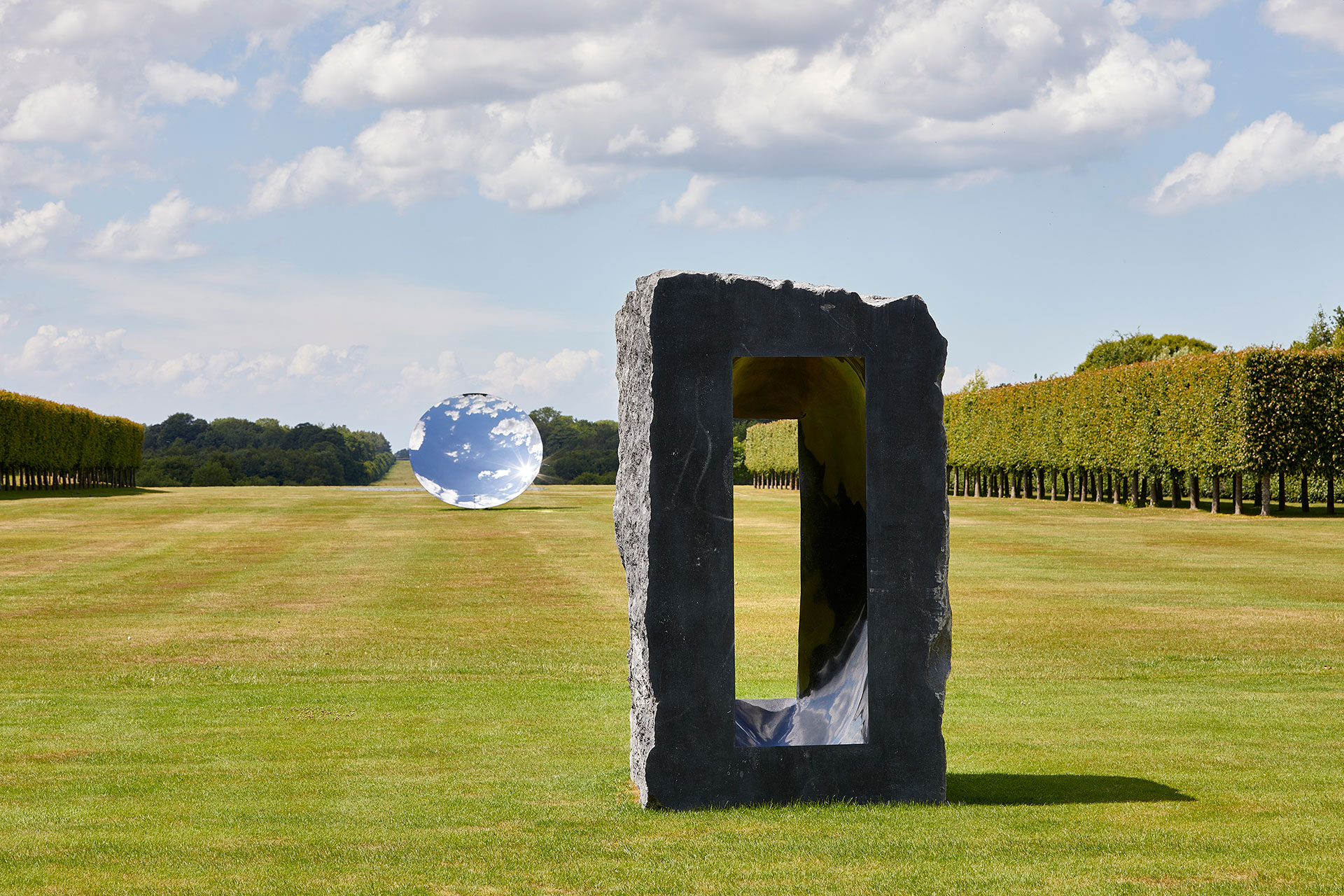 Exhibition view, Anish Kapoor at Houghton Hall. © Anish Kapoor. All rights reserved DACS, 2020. Photo by Pete Huggins. Featured: Untitled, 1997, Kilkenny limestone. Courtesy the artist. Sky Mirror, 2018, stainless steel. Courtesy the artist and Lisson Gallery.