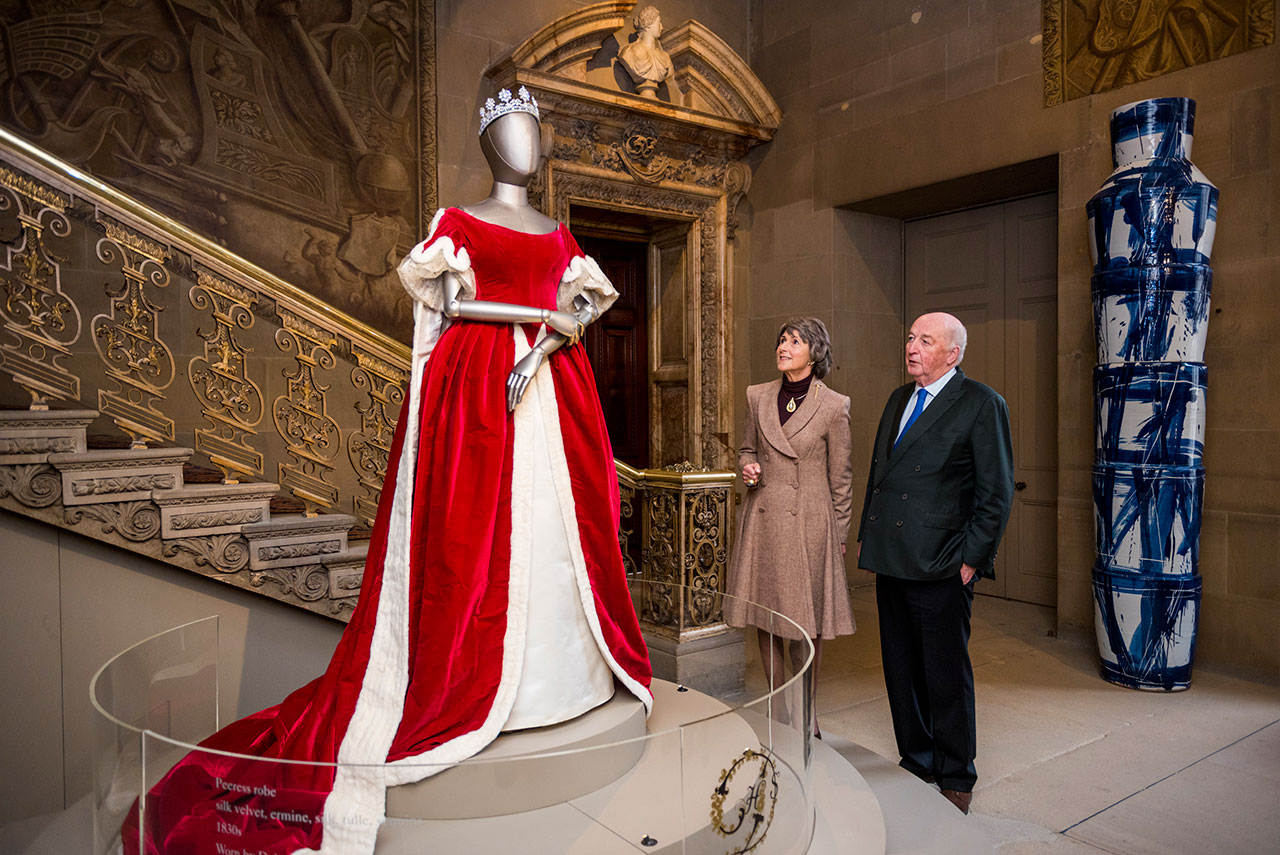 Duke and Duchess of Devonshire with Mistress of the Robes gown worn by Deborah Devonshire for Elizabeth 11 Coronation. Photo courtesy Chatsworth House Trust.