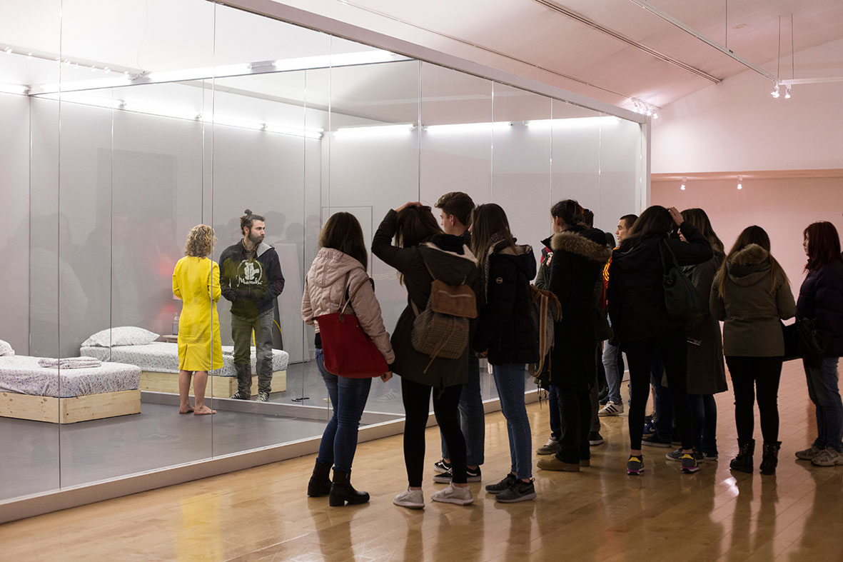 "Audience and a perplexed participant inside the double glass room of actress Yiota Argyropoulou, the setting of her six-week-long performance ""A person at a time"". Part of AS ONE at the Benaki Museum, Athens, 2016. Photo © Natalia Tsoukalas."