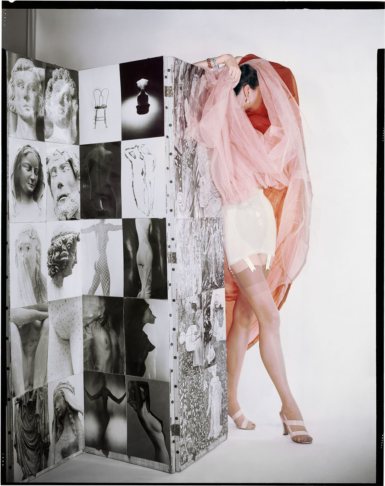 Lily of France Corset, Dior Organdi, Modeltex Low, Valley Sandals. Model: Ruth Knowles. In front of a screen of photographs by Erwin Blumenfeld. Variant of the photograph published in Vogue US February 15, 1953 © The Estate of Erwin Blumenfeld.