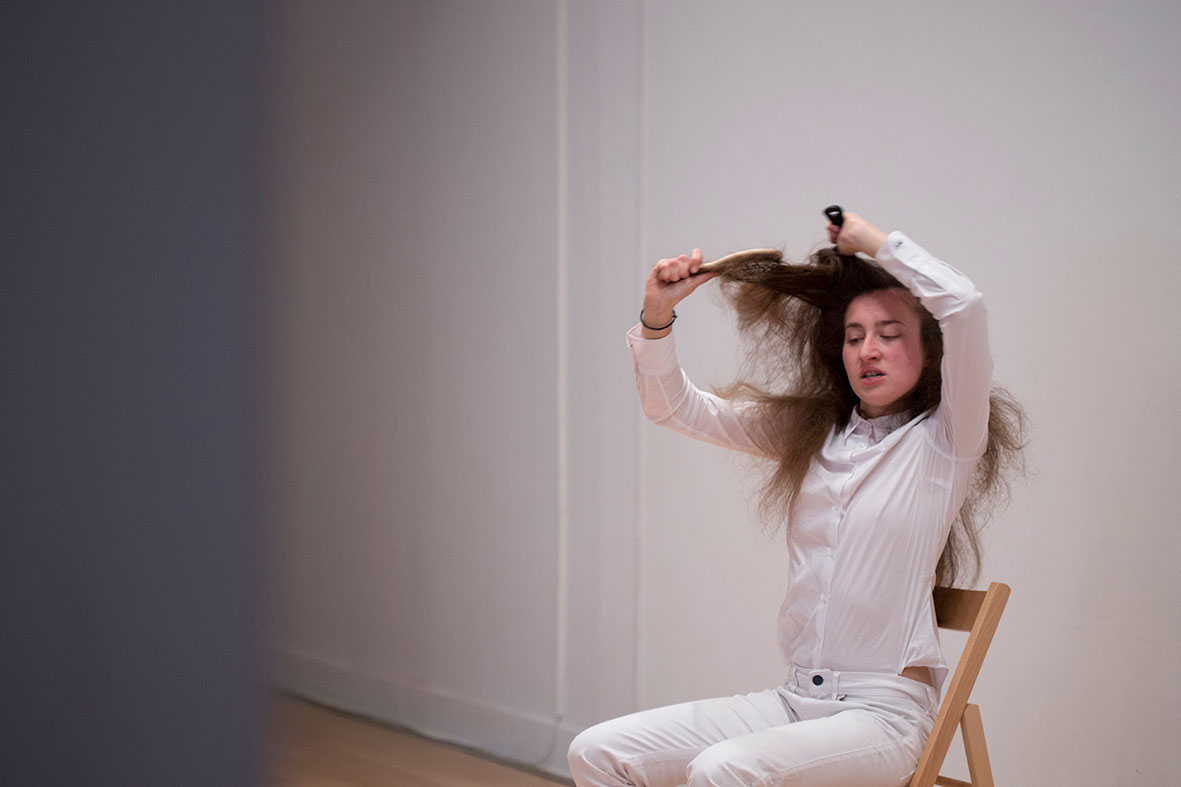 "A re-performance of Marina Abramovic's 1975 work ""Art must be beautiful, artist must be beautiful"" by a younger artist. Photo © Natalia Tsoukalas."