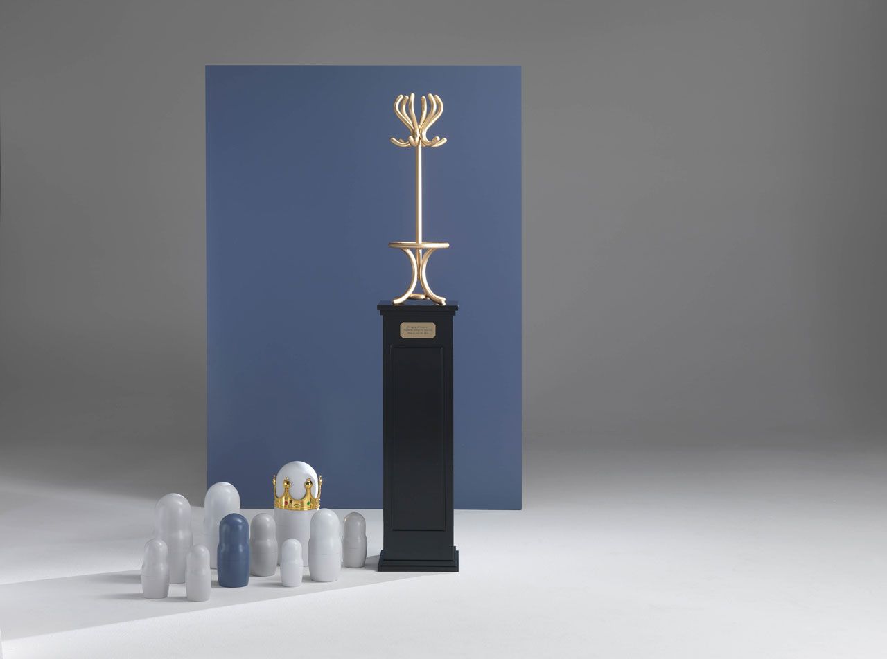 "GALAVER hat and coat stand by Emanuele Magini for JCP Universe.Materials: iron structure in ""tailor made"" gold finish on wooden base in matte black finish. Dimensions (H x W x D):180cm x 30cm x 30cm. GALAVER storytelling picture. Photo by Silvio Macchi, set design by Katia Meneghini © JCP Universe."