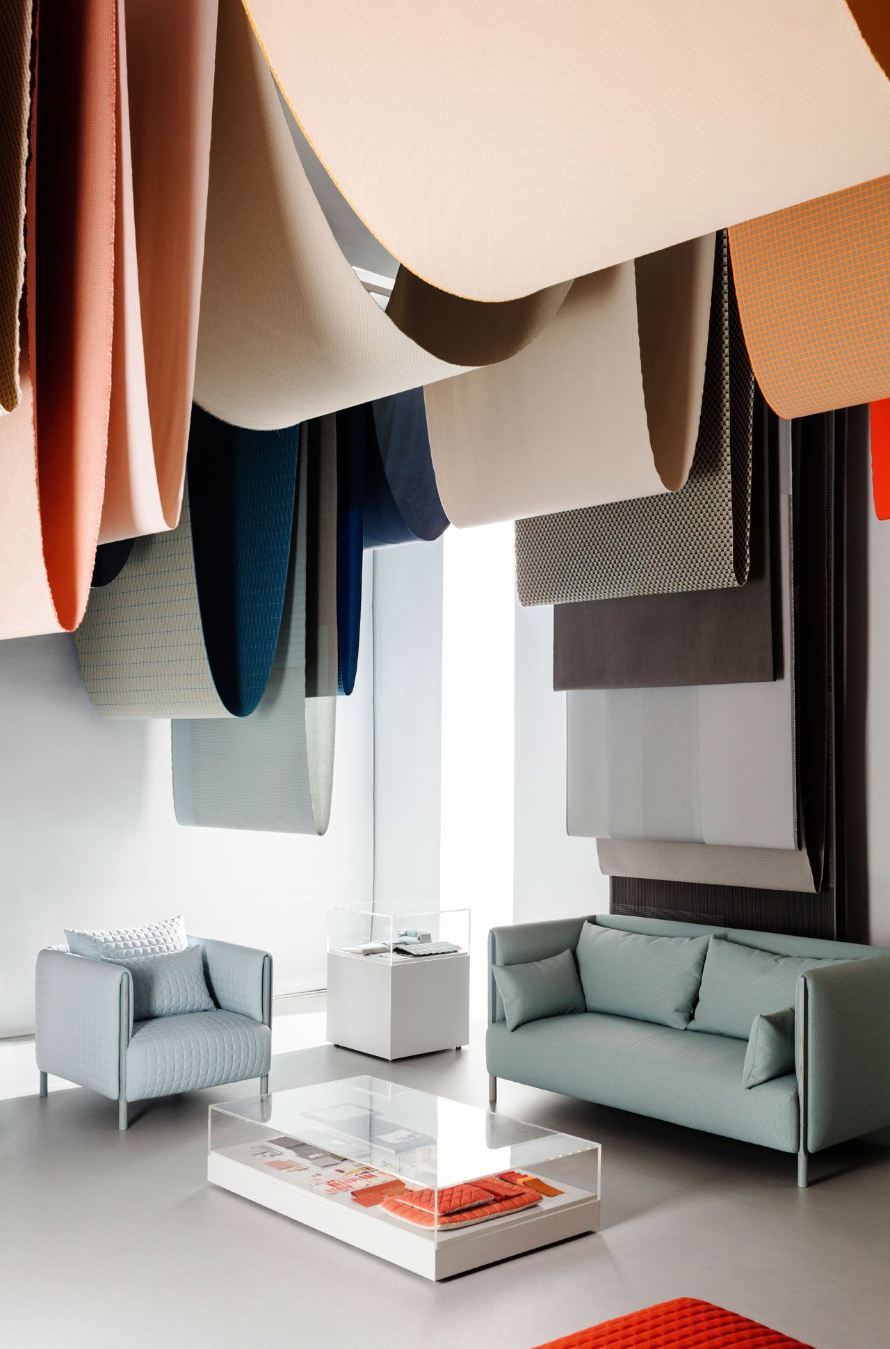 Chromatography exhibit by Stefan Scholten and Carole Baijings of Scholten & Baijings in the Herman Miller featuringMahatma textiles that were hanging from the ceiling, and beneath them elements of their new ColourForm Sofa Group for Herman Miller.Photo by Ben Anders.