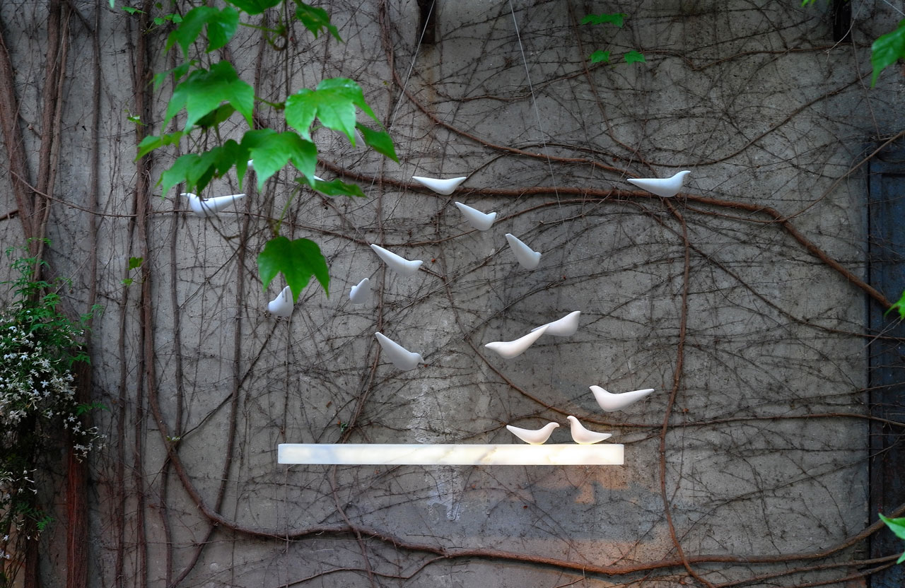 'Ray' installation by on•entropy at the courtyard of Galleria Rossana Orlandi; a pendant light which attracts a flock of marble birds.Photo by Tati Uzlova.