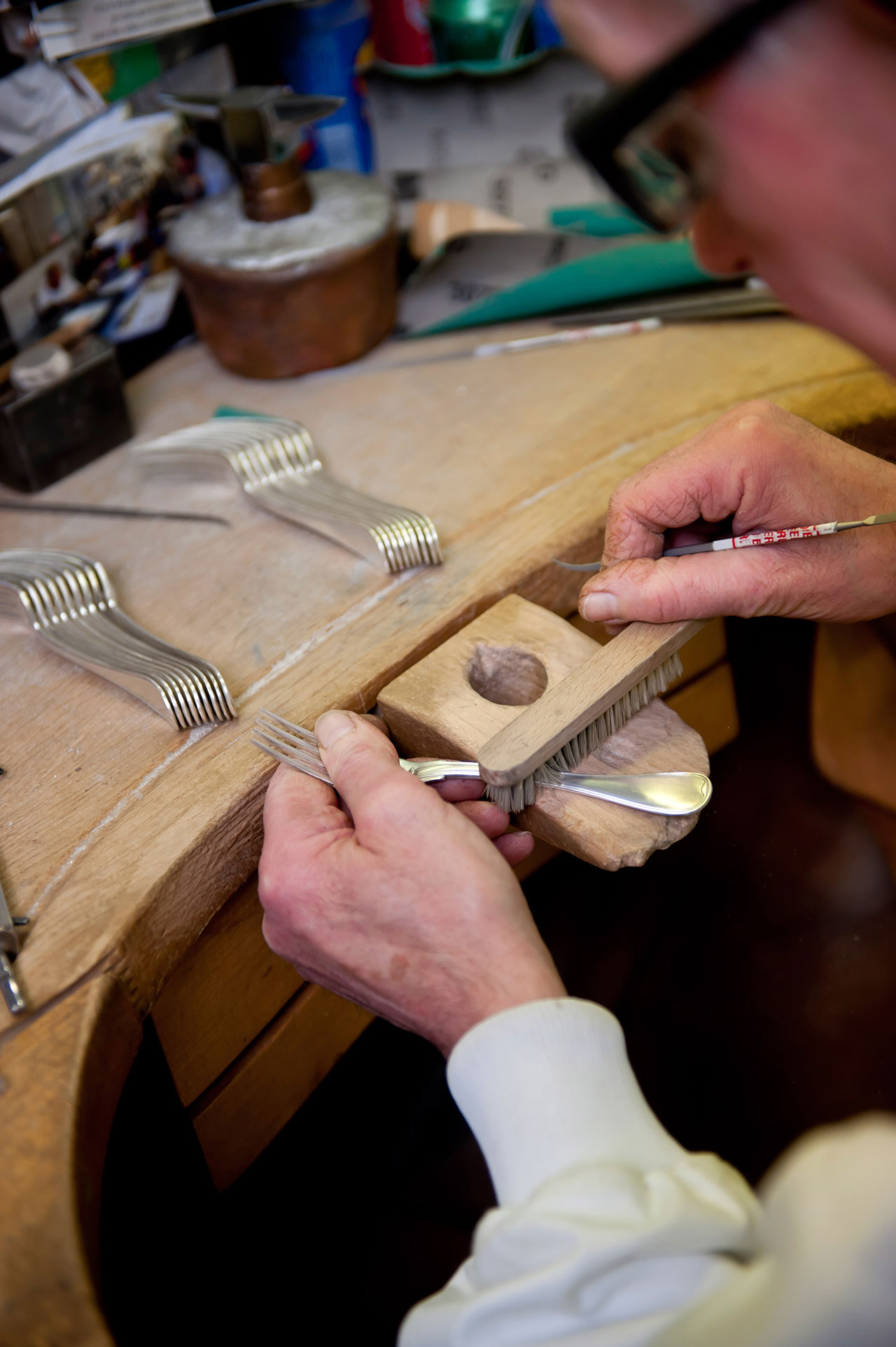 A silversmith working on a set of forks at the Puiforcat workshop. Photo by Alexandre & Emilie {Persona production} for Yatzer. Copyright © Yatzerland Ltd.