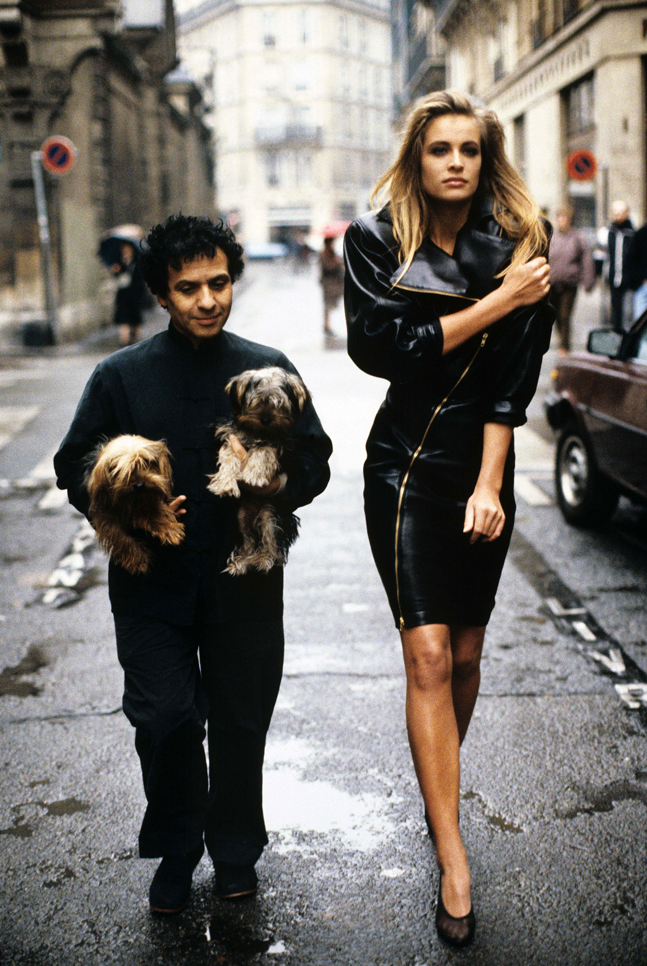 Fashion designer Azzedine Alaia holding his two Yorkshire terriers, Patapouf and Wabo, walking in Paris street with model Frederique who wears one of his creations, a black leather zippered dress, 1986. Photo by Arthur Elgort.
