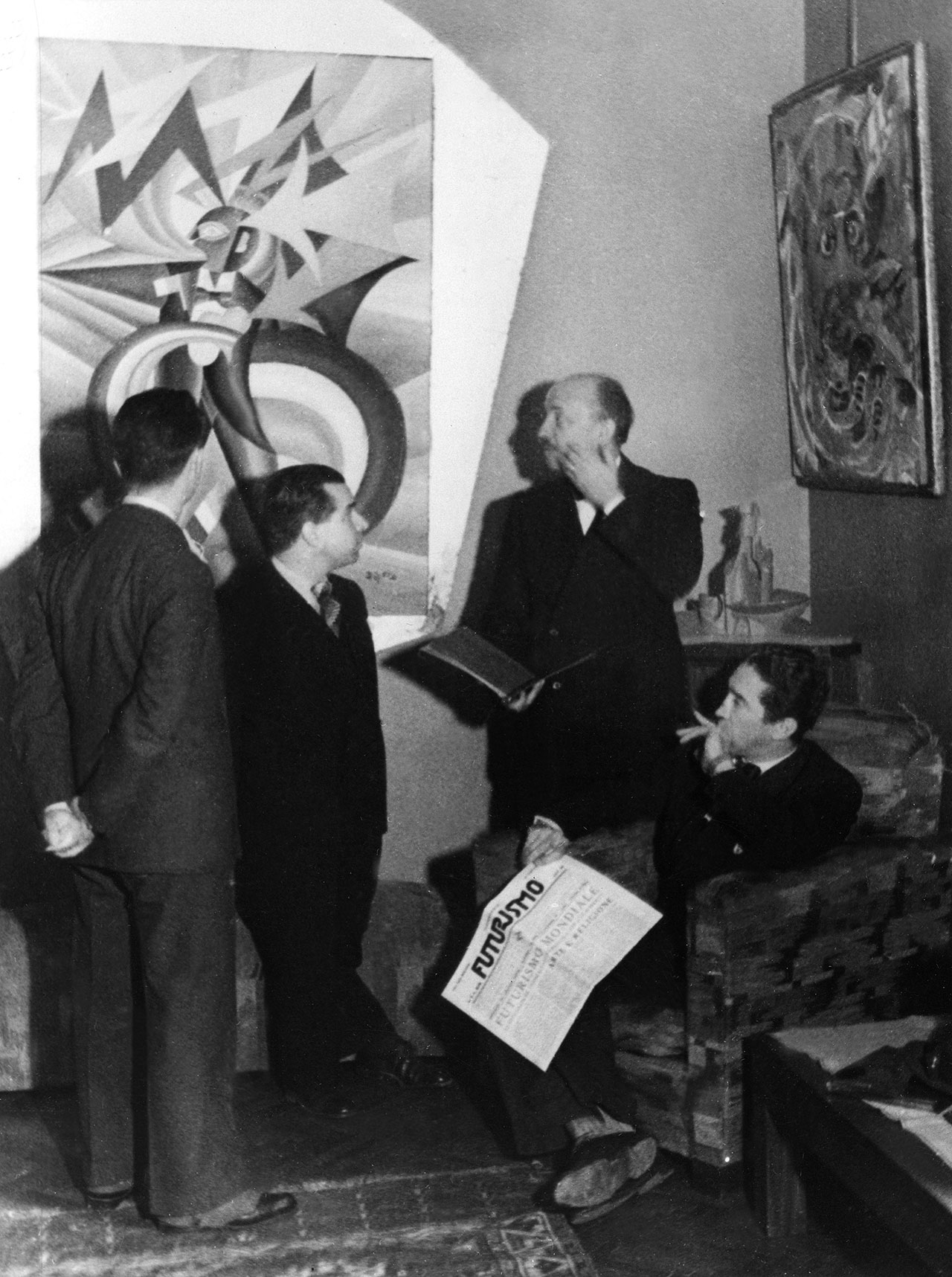 Filippo Tommaso with the editorial team of the magazine 'Futurismo'. From right: Mino Somenzi, Filippo Tommaso Marinetti, Enrico Prampolini and Bruno G. Sanzin (back) In the photo the work Marinetti temporale patriottico, Ritratto psicologico (1924) by Fortunato Depero - For the work © Fortunato Depero by SIAE 2018 Photo: Felix H. Man - Koester - 1931 Ullstein Bild - Felix H. Man /Archivi Alinari, Firenze.