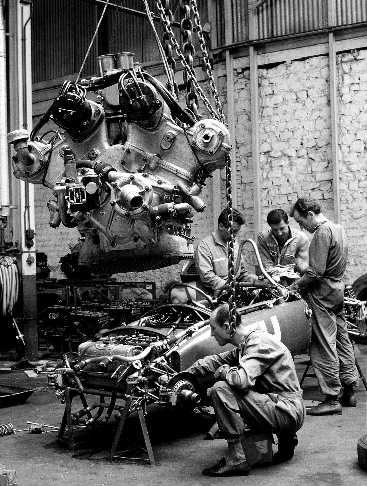 The car is the 156 F1, no. 50; The engine hanging, in the foreground, is 6-cylinder V of 65. Photo courtesy of Ferrari.